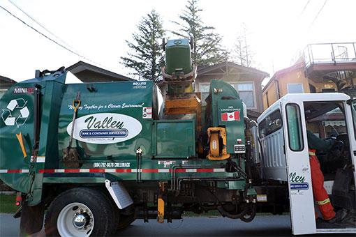 curbside garbage truck picking up residential garbage bins